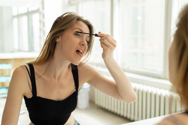 Schönes Mädchen malt Wimpern und Augenbrauen am Spiegel macht Gesichter lustig lizenzfreies stockbild