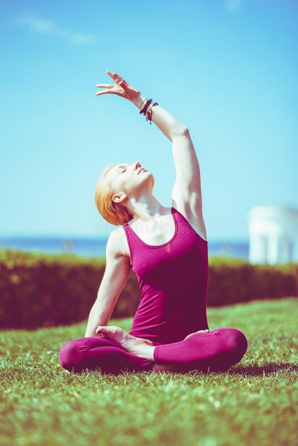 Schönes Mädchen meditiert im Lotussitz, der auf Gras am sonnigen Tag sitzt stockbilder
