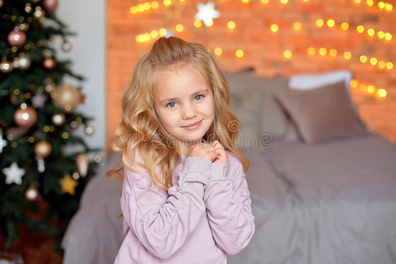 Schönes Mädchen mit blonden Locken in der Erwartung von Geschenken in den Hintergrund Weihnachtslichtern und -bett Neues Jahr und lizenzfreie stockfotos