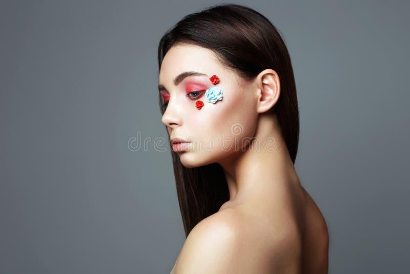 Schönes Mädchen mit Blumen auf dem Gesicht  lizenzfreie stockfotografie