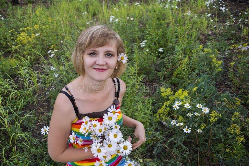 Schönes Mädchen mit Blumenkamille in ihrem Haar stockfotos