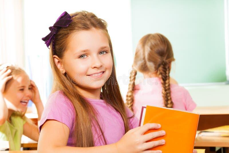 Schönes Mädchen mit dem Bogen, der zurück in der Klasse schaut lizenzfreies stockbild