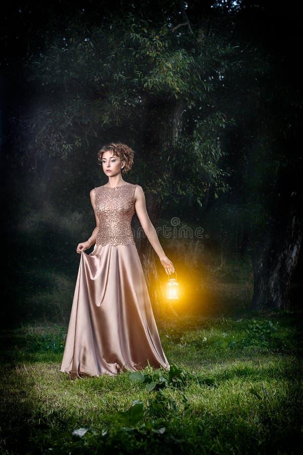 Schönes Mädchen mit dem braunen gelockten Haar im wunderbaren Kleid mit Lampen beleuchten im Märchenwaldkunstfoto stockbild
