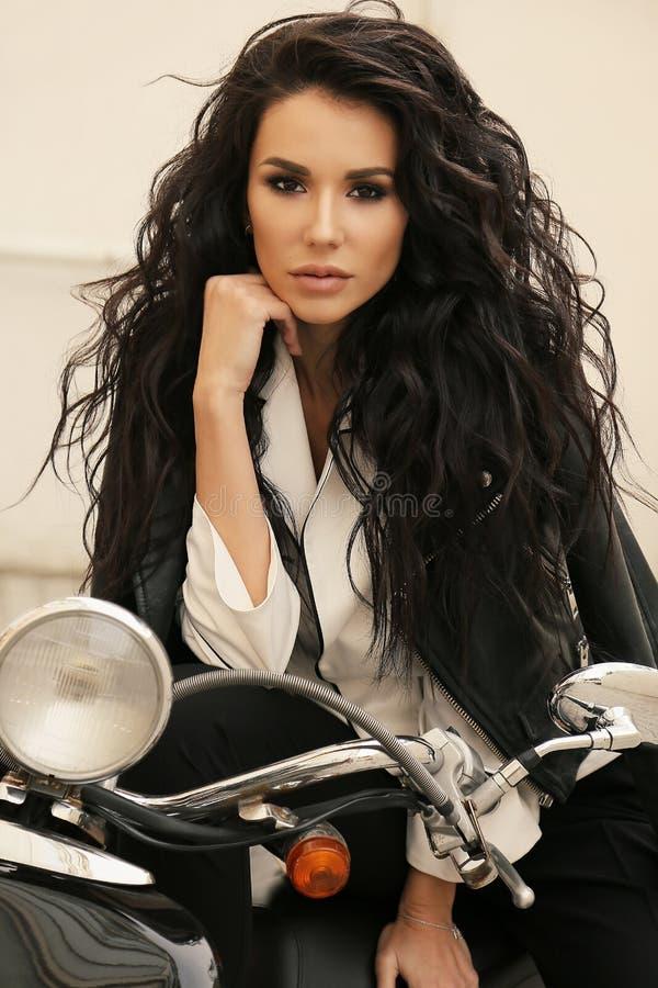Schönes Mädchen mit dem dunklen Haar in der eleganten Kleidung, die am autum aufwirft stockfotografie