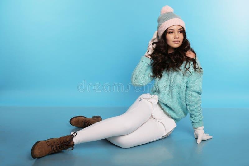 Schönes Mädchen mit dem gelockten Haar im warmen gemütlichen Winter kleidet lizenzfreie stockbilder