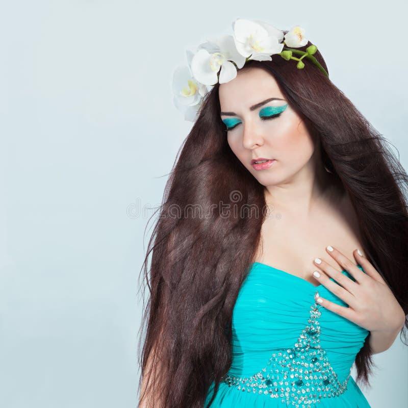 Schönes Mädchen mit dem gesunden dunklen Haar und den Orchideen lizenzfreies stockfoto