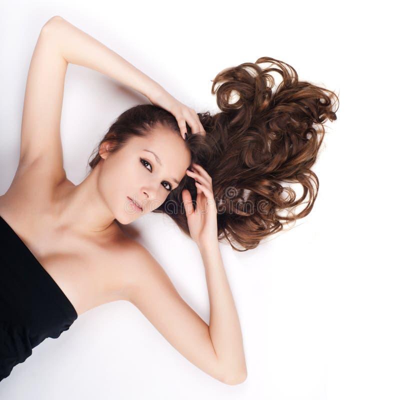 Schönes Mädchen mit dem langen Haar, das auf dem Boden liegt stockfotos
