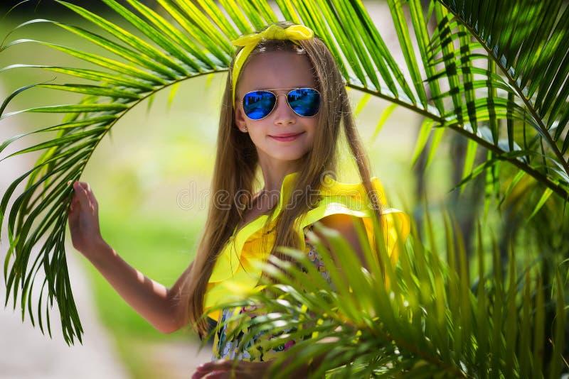 Schönes Mädchen mit dem langen Haar in einem gelben Badeanzug und in einer mehrfarbigen Sonnenbrille auf dem Hintergrund von Palm stockfoto