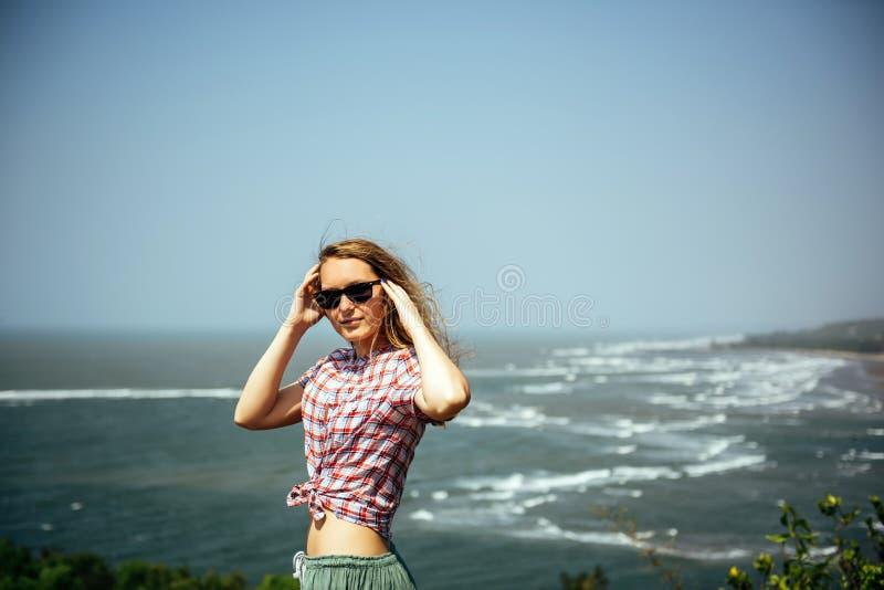 Schönes Mädchen mit dem nackten sexy Bauch, der auf Seefelsen sich entspannt stockbilder