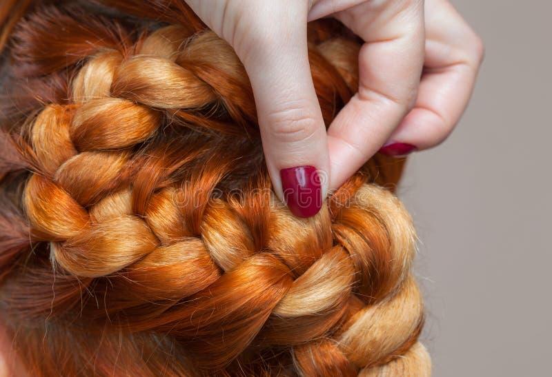 Schönes Mädchen mit dem roten Haar, Friseur spinnt eine Zopfnahaufnahme, in einem Schönheitssalon lizenzfreie stockbilder