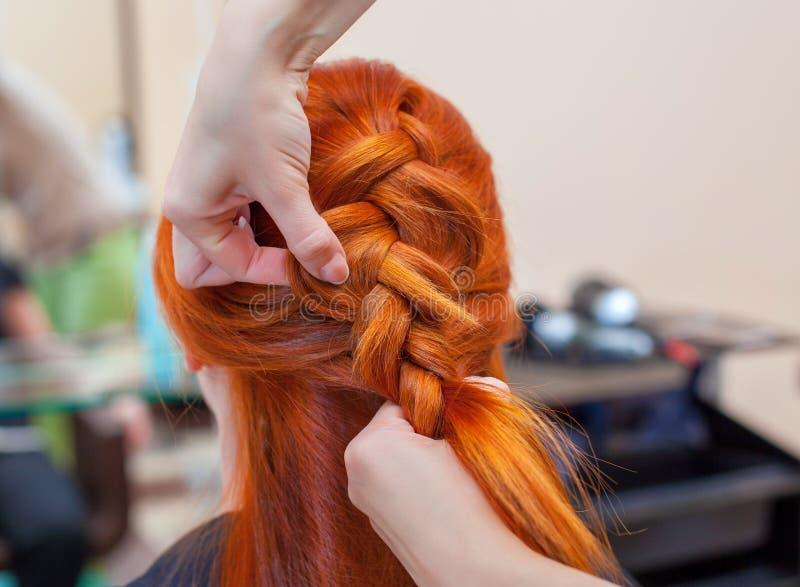 Schönes Mädchen mit dem roten Haar, Friseur spinnt eine Zopfnahaufnahme, in einem Schönheitssalon stockfoto
