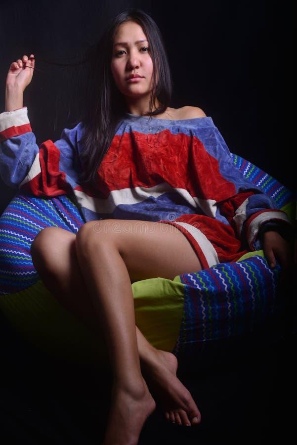 Schönes Mädchen mit den langen Beinen und schwarzen dem Haar, die in der Bohnentasche in einer gemütlichen Atmosphäre sitzt lizenzfreie stockfotos