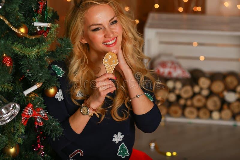 Schönes Mädchen mit den Plätzchenhänden sitzt nahe einem Weihnachtsbaum und einem Lächeln stockfotografie