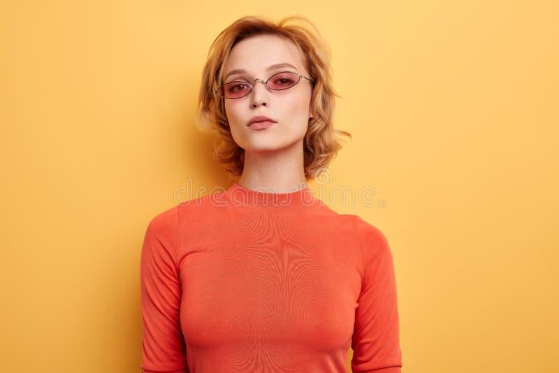 Schönes Mädchen mit den rosa Gläsern, welche die Kamera betrachten lizenzfreies stockbild