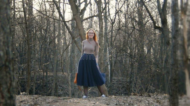 Schönes Mädchen mit den tragenden Gläsern des roten Haares, die im Frühjahr Park stehen stockbilder
