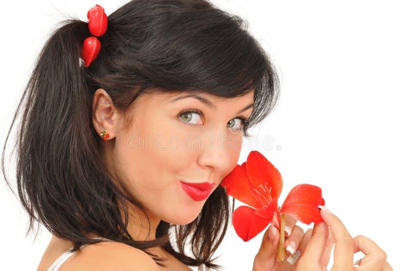 Schönes Mädchen mit der roten Blume, die Kamera betrachtet stockfotografie