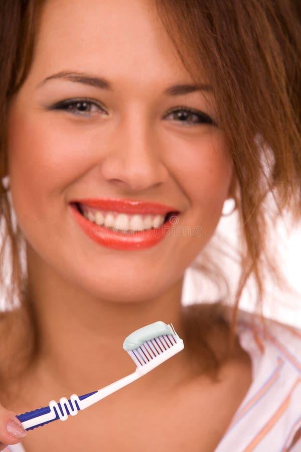 Schönes Mädchen mit der Zahnbürste getrennt auf Weiß stockfoto