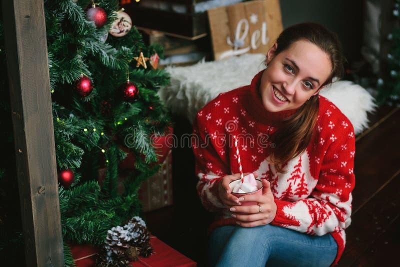 Schönes Mädchen mit Eibisch in den Händen lächelnd nahe dem Weihnachtsbaum lizenzfreie stockfotografie