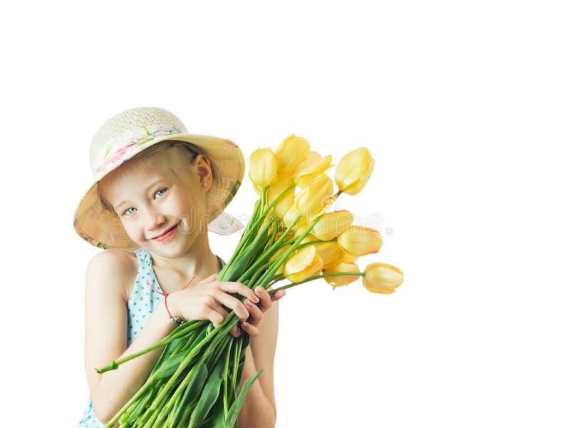 Schönes Mädchen mit einem Blumenstrauß von gelben Tulpen stockbilder