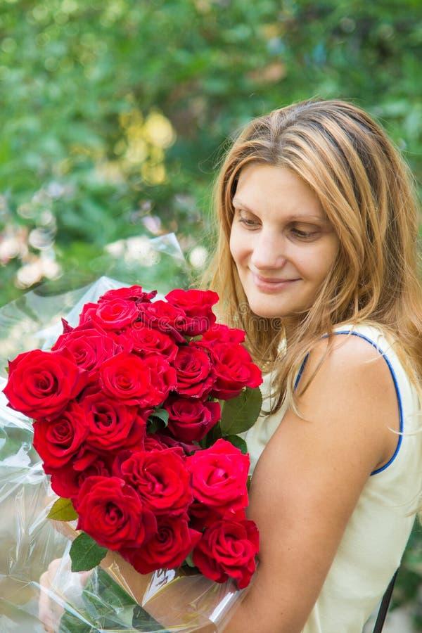 Schönes Mädchen mit einem Blumenstrauß von roten Rosen lizenzfreie stockfotografie