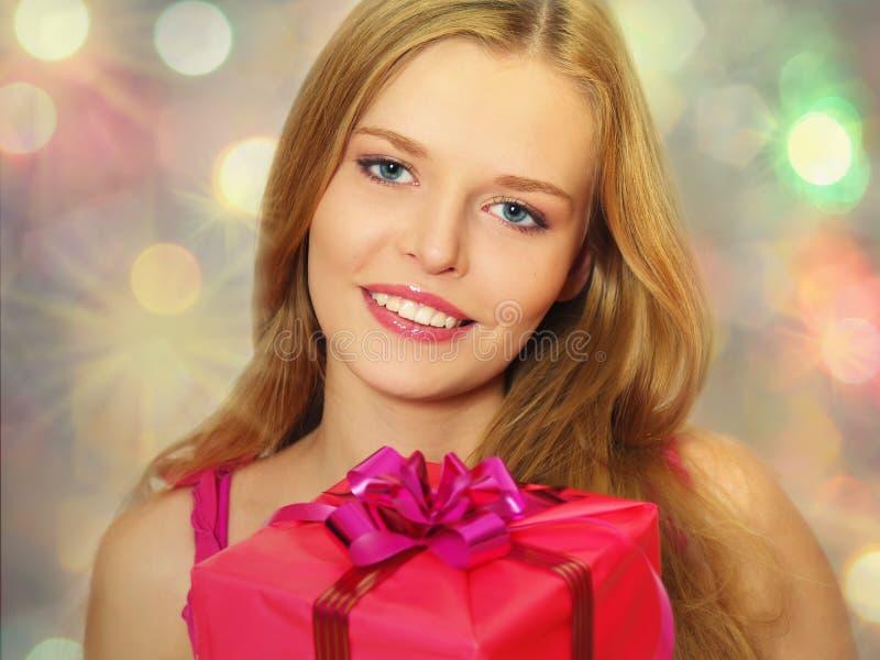 Schönes Mädchen mit einem Geschenk in den Händen stockfotos