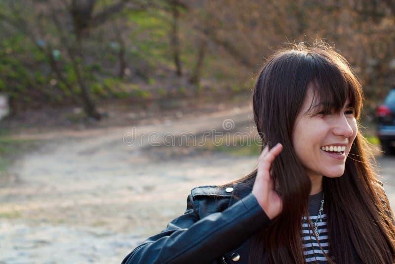 Schönes Mädchen mit einem Knall und einem langen Haar lacht in einer Weste und in einer Lederjacke lizenzfreie stockbilder