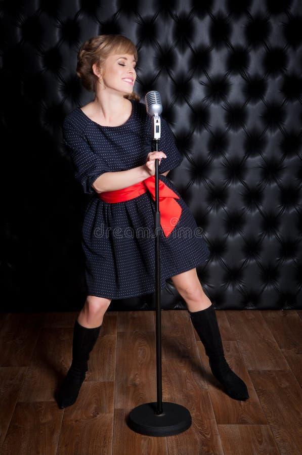 Schönes Mädchen mit einem Mikrofon auf Stadium stockfotografie