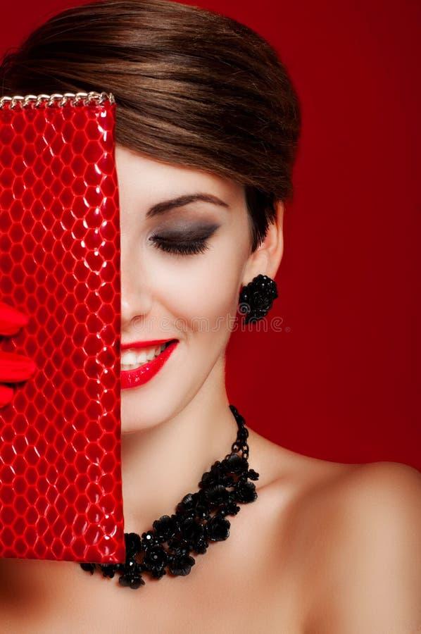 Schönes Mädchen mit einem roten Geldbeutel verfassung zubehör lizenzfreie stockfotos