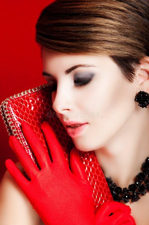 Schönes Mädchen mit einem roten Geldbeutel verfassung zubehör lizenzfreie stockbilder