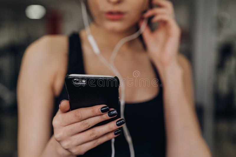 Schönes Mädchen mit einem Telefon in der Turnhalle stockfotos
