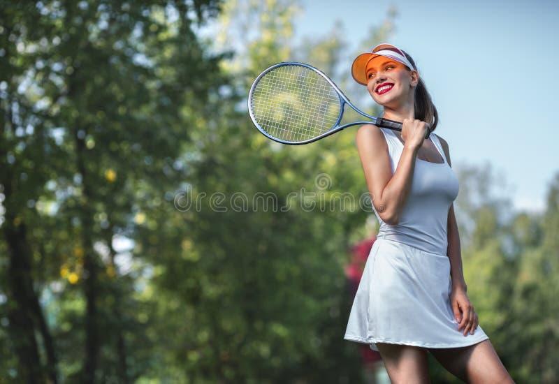 Schönes Mädchen mit einem Tennisschläger lizenzfreie stockfotos