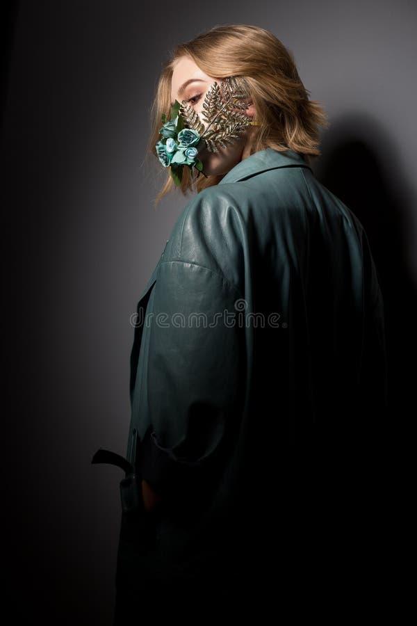 Schönes Mädchen mit einer Blumenmaske auf einem dunkelgrauen Hintergrund lizenzfreies stockfoto