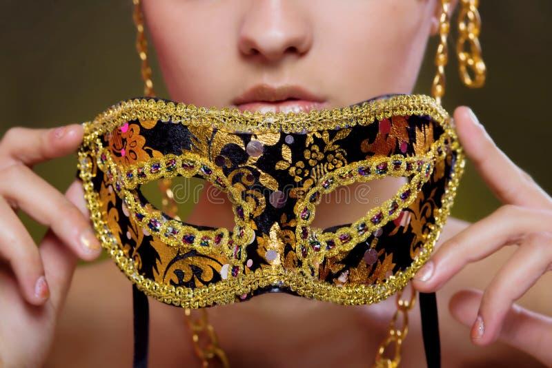 Schönes Mädchen mit einer Maskerademaske stockfoto