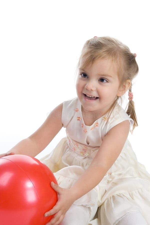 Schönes Mädchen mit einer roten Kugel stockfoto