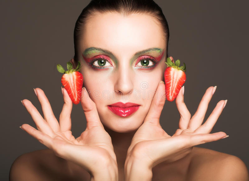Schönes Mädchen mit Erdbeere stockfotografie