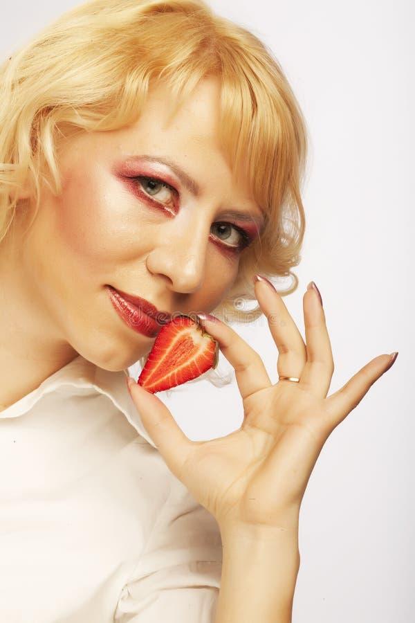 Schönes Mädchen mit Erdbeere stockbilder