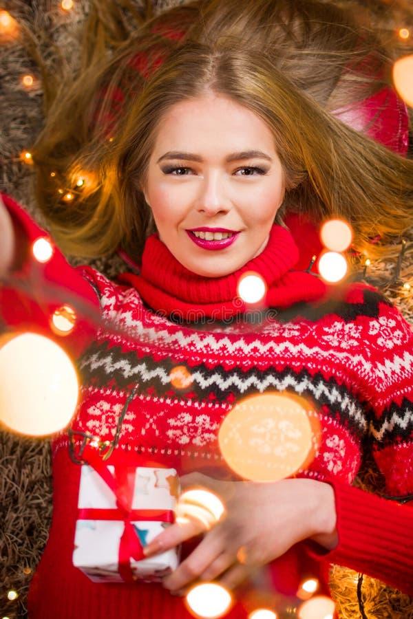 Schönes Mädchen mit festlichen Lichtern auf dem Teppich stockfotos