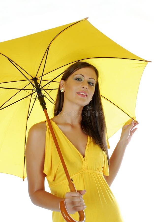 Schönes Mädchen mit gelbem Regenschirm lizenzfreie stockfotografie