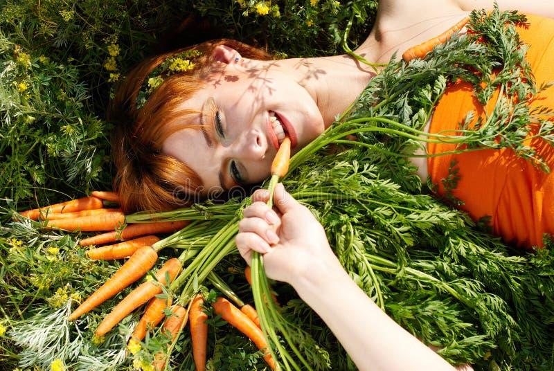 Schönes Mädchen mit geschmackvoller Karotte lizenzfreies stockbild