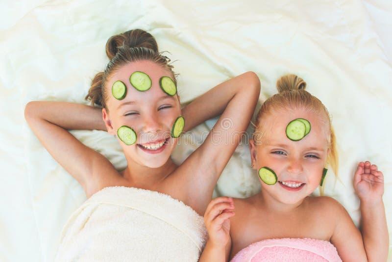 Schönes Mädchen mit Gesichtsschablone der Gurke lizenzfreies stockfoto