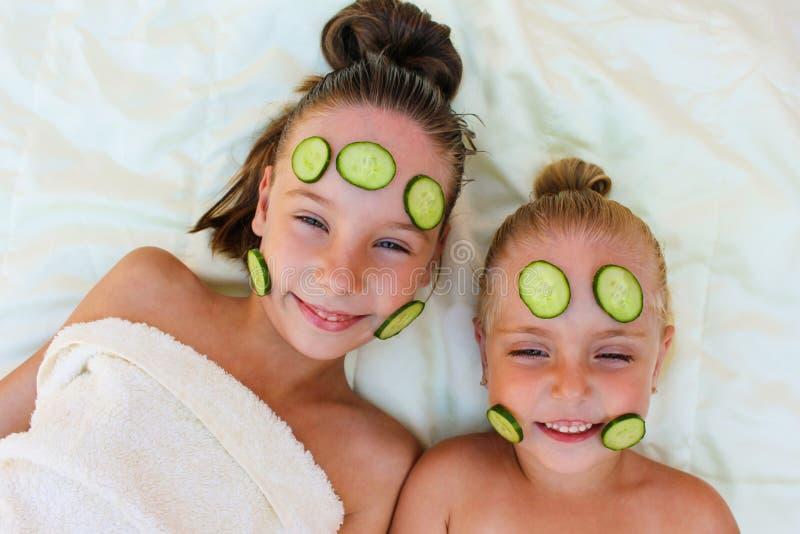 Schönes Mädchen mit Gesichtsschablone der Gurke lizenzfreie stockbilder