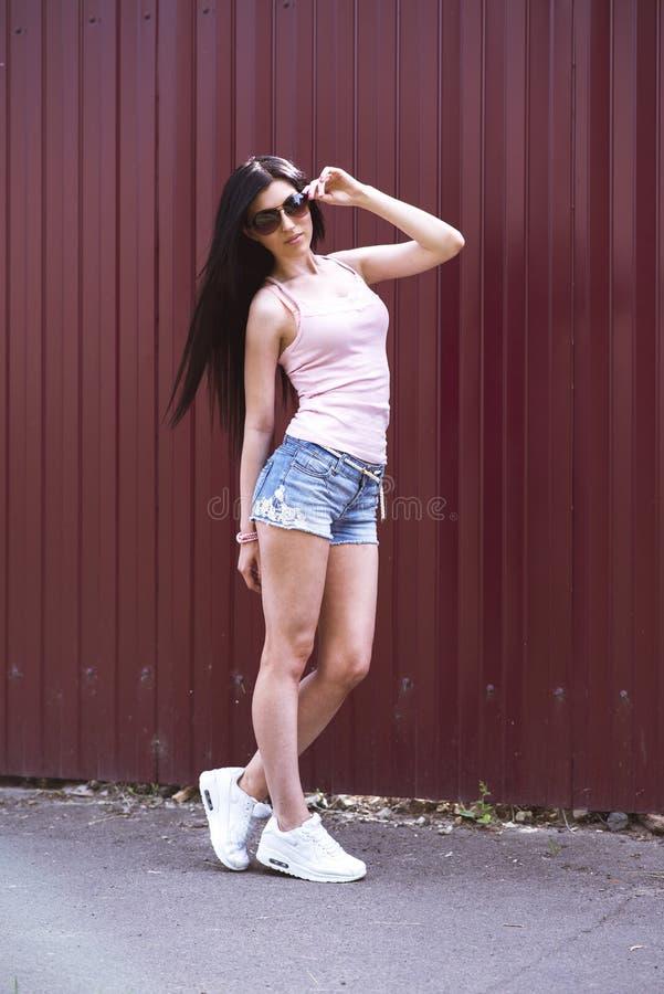 Schönes Mädchen mit Glaskurzen hosen und rosa Bluse steht vor einem Bretterzaun, stilvolle Mode Turnschuhe lizenzfreie stockfotografie