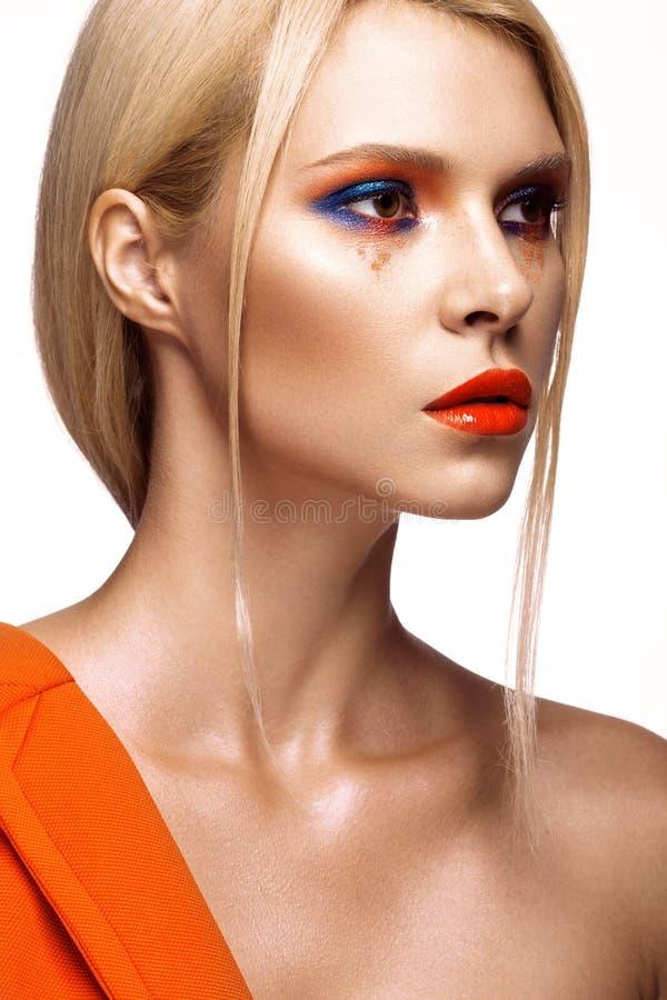 Schönes Mädchen mit hellem farbigem Make-up und den orange Lippen Schönes lächelndes Mädchen lizenzfreies stockbild
