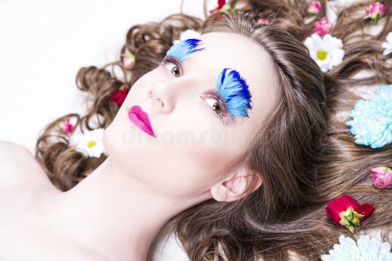Schönes Mädchen mit kreativem Make-up und Frisur mit Blumen stockfotos