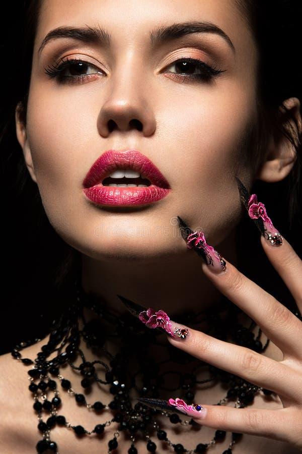 Schönes Mädchen mit langen Nägeln und den sinnlichen Lippen stockfoto