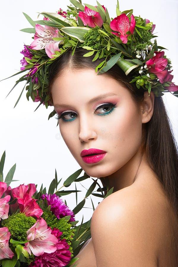 Schönes Mädchen mit perfekter Haut und heller Blumenkranz auf ihrem Kopf stockfoto