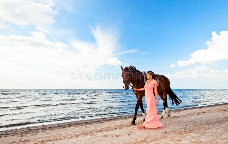 Schönes Mädchen mit Pferd auf Seeküste lizenzfreie stockfotografie