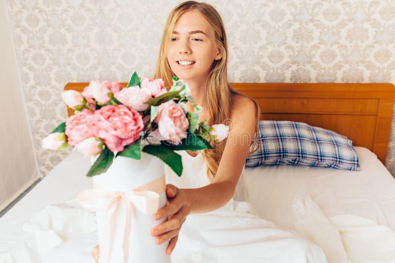 Schönes Mädchen mit Pfingstrose blüht das Sitzen auf dem Bett Sie gerade w lizenzfreie stockbilder