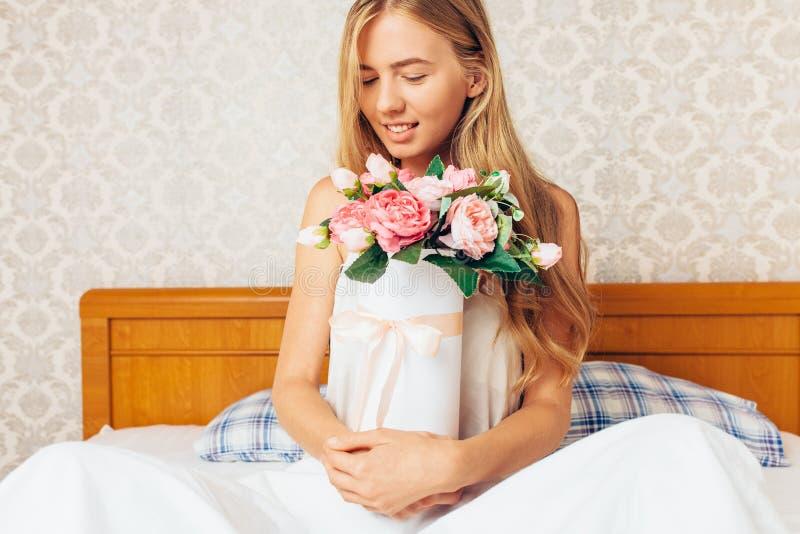 Schönes Mädchen mit Pfingstrose blüht das Sitzen auf dem Bett Sie gerade w lizenzfreie stockfotografie