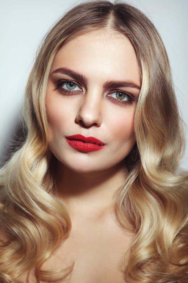 Schönes Mädchen mit rotem Lippenstift und dem blonden gelockten Haar lizenzfreies stockfoto